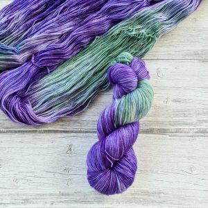 One hanked skein of yarn in the colorway Lavender Fields laying on top of another opened skein of Lavender Fields