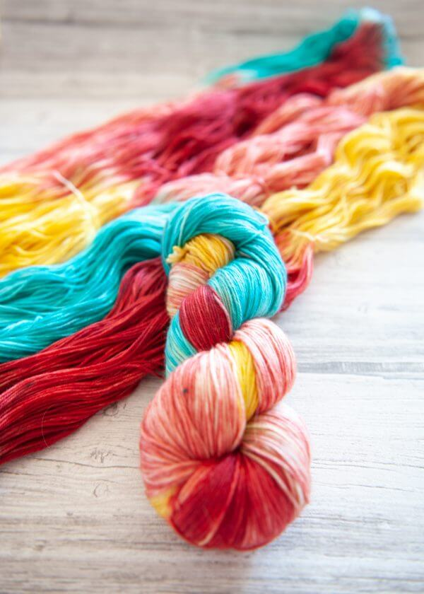 One hanked skein of yarn in the colorway Roussillon laying on top of another opened skein of Roussillon