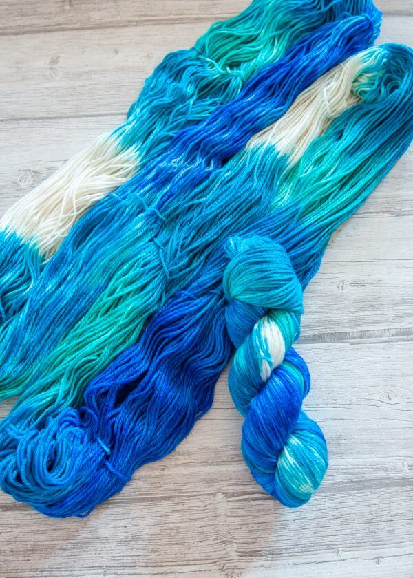 One hanked skein of yarn in the colorway Cote d'Azur laying on top of another opened skein of Cote d'Azur
