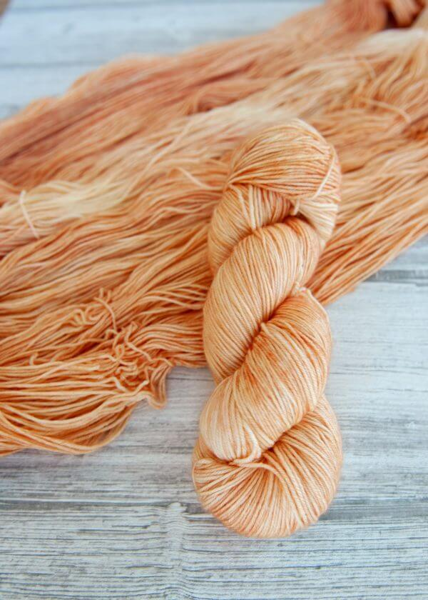 One hanked skein of yarn in the colorway Rosé laying on top of another opened skein of Rosé