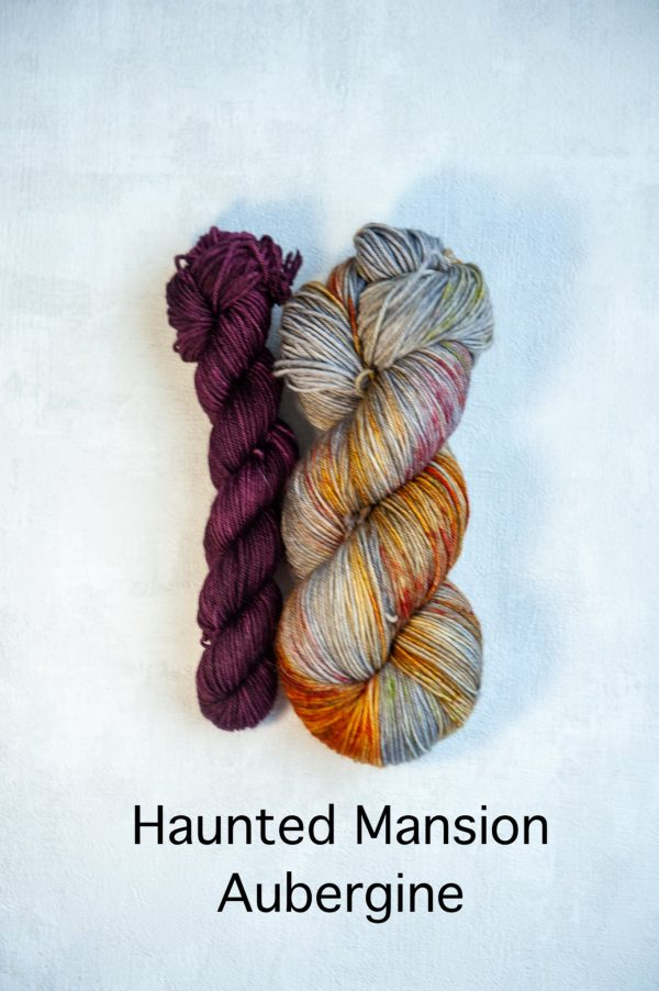 A sock set with the main skein in grey with red and brown specklesand a mini skein in purple