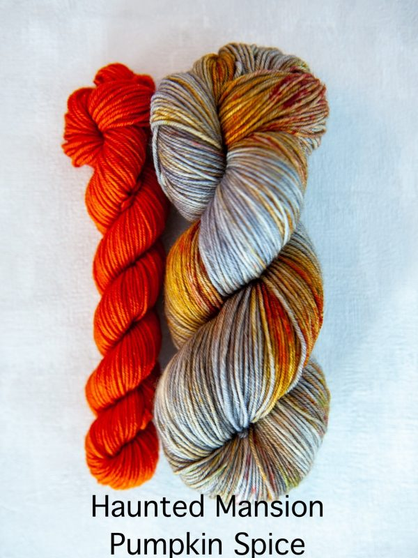 A sock set with the main skein in grey with red and brown speckles and a mini skein in orange