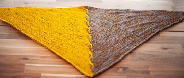 Edge of Winter shawl laid flat, left half of the triangular shawl is yellow, right half is grey