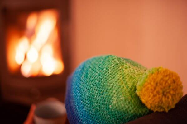 Person wearing the Eye of Partridge hat while sitting in front of a fire, photographed from behind