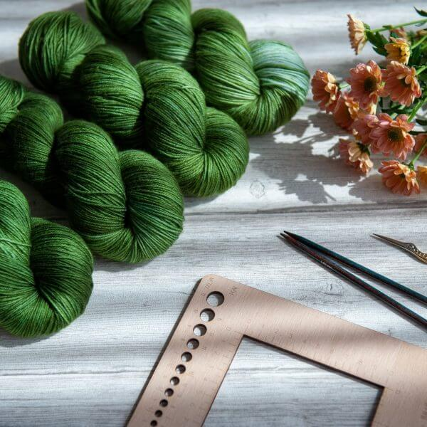 Four skeins of yarn in varying shades of green laying next to some flowers and knitting notions