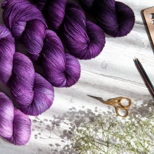 Five skeins of yarn in varying shades of purple laying next to some flowers and knitting notions