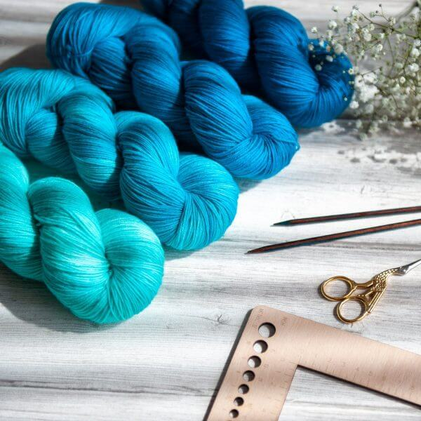 Four skeins of yarn in varying shades of blue laying next to some flowers and knitting notions
