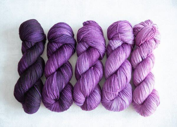 Five skeins in varying shades of purple