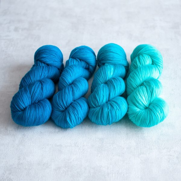 Four skeins of yarn in varying shades of blue