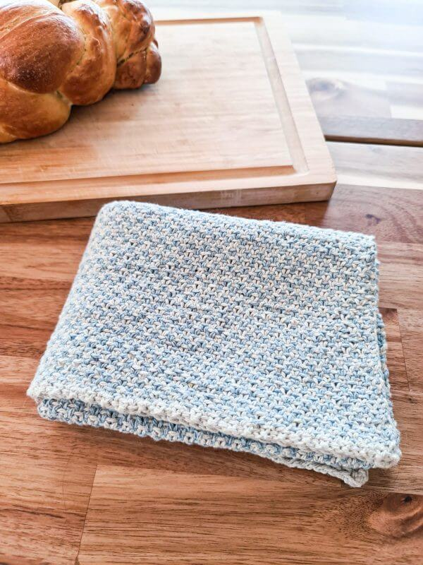 A folded up Cottage Tea Towel laying next to a loaf of bread
