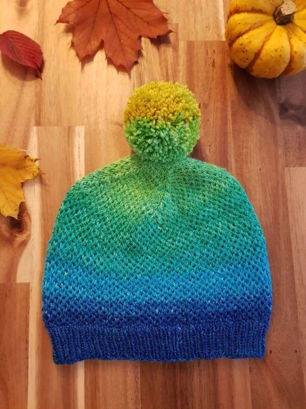The Eye of Partridge Hat laid flat with leaves surrounding it