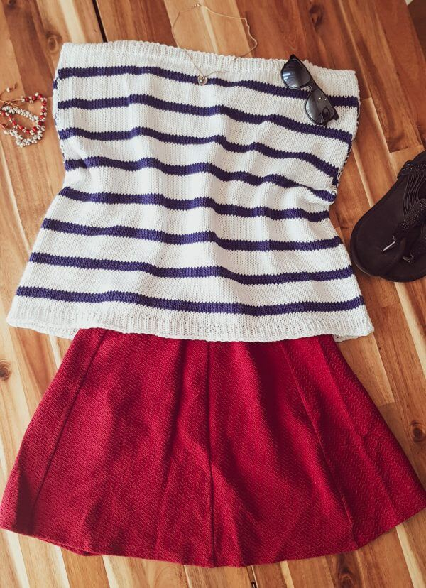 The knitted Harbor Top laid flat with a red skirt and sandals