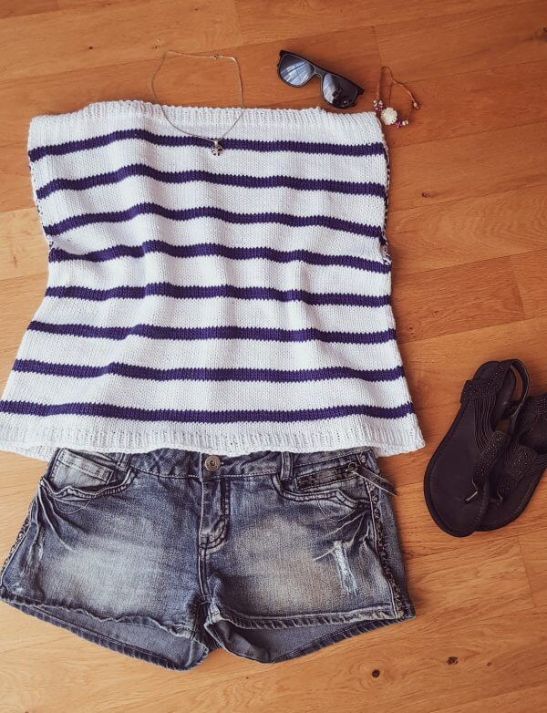 The knitted Harbor Top laid flat with a pair of jeans shorts and sandals