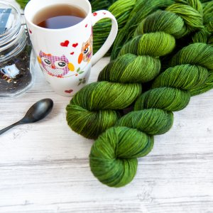 two skeins of yarn in the colorway 'Nessie' next to a cup of tea