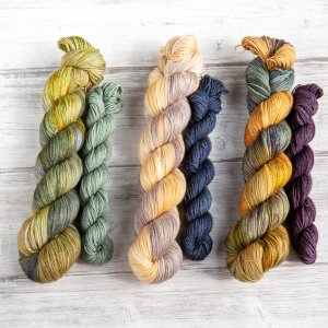 Three sock set yarns next to each other, each consisting of a main and a mini skein