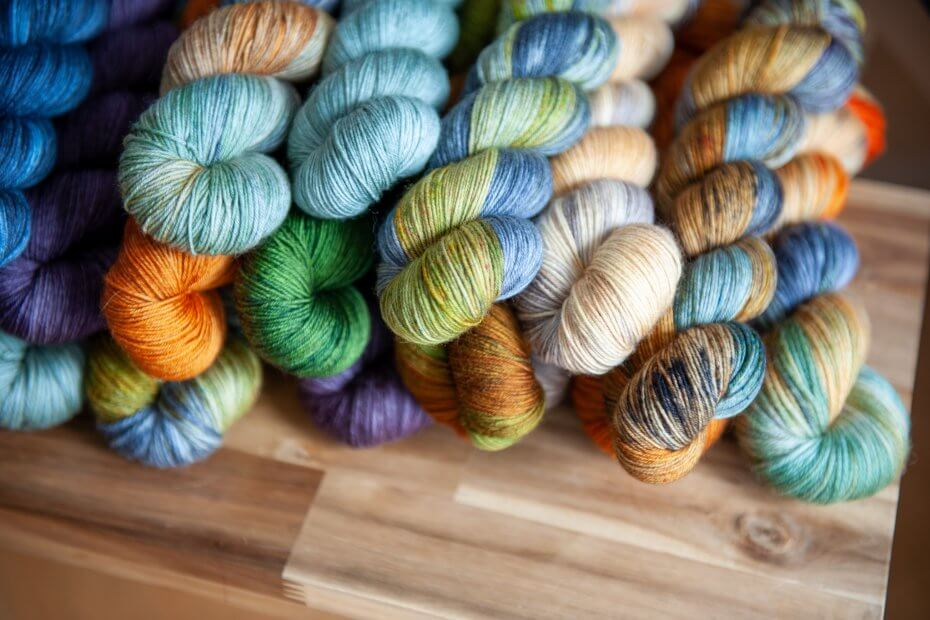 Multiple skeins of yarns laying on top of a wooden bench