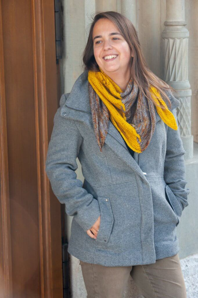 Woman wearing the two-colored Edge Of Winter Shawl and a grey coat, leaning against a wall.