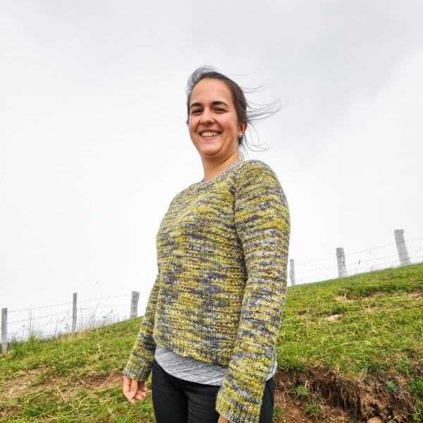 woman wearing a green and grey sweater standing in a green pasture with foggy grey sky